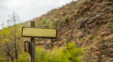 maquete de sinal direcional de montanha com teias de aranha penduradas foto