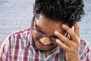 jovem sofrendo de dor de cabeça foto