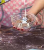 mulher servindo leite em pedaços de chocolate em uma tigela de vidro
