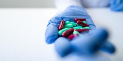 mão da enfermeira cheia de comprimidos verdes e vermelhos com luva azul em fundo branco