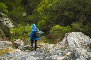 garota caminhando na montanha enquanto chove com vegetação