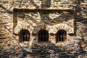 arcos de janela de pedra com sombras de árvores foto