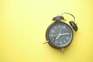 despertador em um fundo amarelo foto