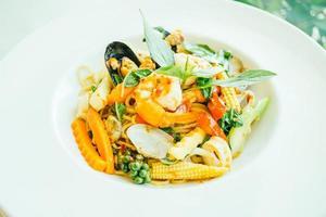espaguete picante de frutos do mar ou macarrão em prato branco foto
