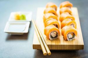 salmão peixe carne sushi roll maki no prato de madeira