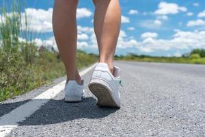 mulher caminhando em uma pequena estrada rural com fundo de céu azul foto