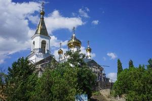 uma igreja com cúpulas douradas cercada por árvores em koktebel, na Crimeia foto