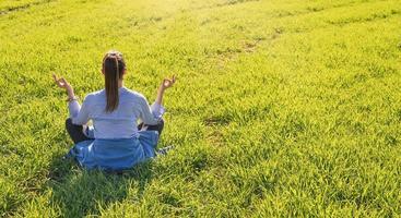 menina sentada em um prado verde na primavera com pose de meditação