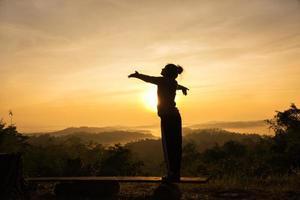 silhueta de mulher torcendo livre com os braços abertos ao nascer do sol no pico da montanha foto