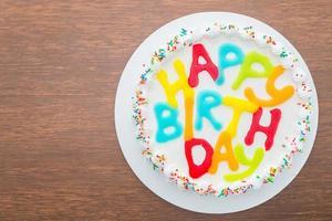 bolo de feliz aniversário em fundo de madeira foto
