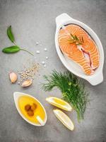 Filé de salmão cru em uma tigela branca com ingredientes para cozinhar em fundo de concreto