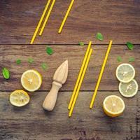 Limão fresco fatiado e folhas de hortelã-pimenta dispostas em um fundo de madeira surrado.