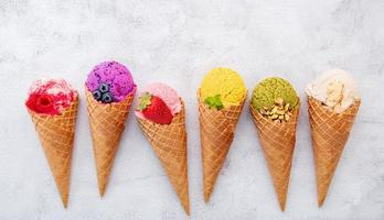 vários sabores de sorvete em cones em fundo de pedra branca