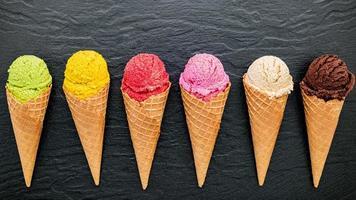 vários sabores de sorvete em cones em fundo de pedra escura