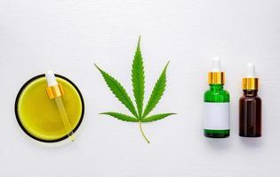 garrafa de vidro de óleo de cannabis e folhas de cânhamo montada em fundo branco