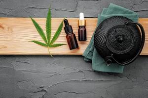 bule vintage com chá de ervas de cannabis e folhas de maconha fresca montado no fundo de concreto