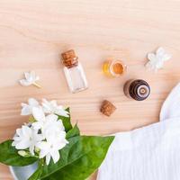 garrafas de óleo de aroma arranjadas com flores de jasmim em fundo de madeira foto