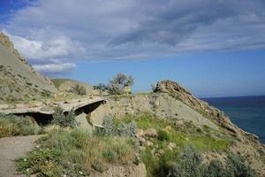 estrada quebrada no meio de colinas vulcânicas ao lado de um corpo de água com um céu azul nublado foto