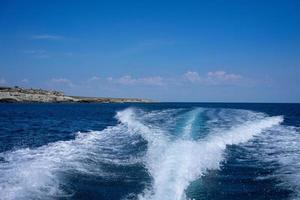 vista da esteira de um barco na água com céu azul nublado foto