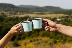 casal brindando com xícaras de café foto