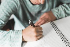 criança cortada escrevendo no caderno foto