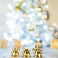 sinos decorativos perto da árvore de natal foto