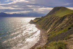 vista do mar, uma praia e montanhas com um céu azul nublado perto de ordzhonikidze, na Crimeia foto