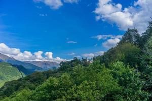 paisagem de montanhas e árvores contra um céu azul nublado foto
