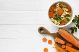 tigela de cenoura de brócolis fusilli plano com espaço de cópia foto