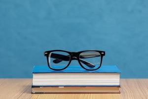 vista frontal de livros com óculos com fundo azul