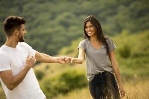 jovem casal apaixonado caminhando pelo campo de grama