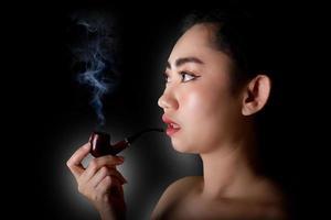 mulher fumando tabaco para cachimbo em fundo preto foto