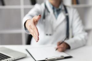 médico close-up esperando para apertar a mão do paciente