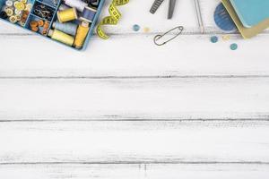 material de costura plano na mesa de madeira foto