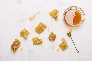 frasco de vidro cheio de mel com colher de mel no fundo branco foto