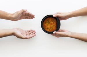 mão dando uma tigela de sopa para uma pessoa necessitada foto