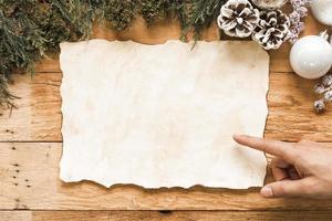 mão perto de papel de fundo de decorações de natal foto