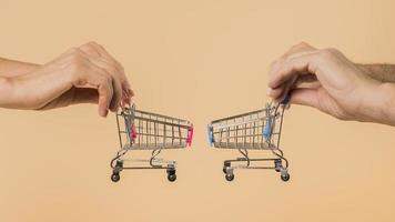 mãos segurando carrinhos de compras em fundo cor de pêssego foto