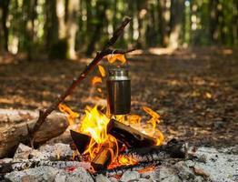 aquecendo água perto da fogueira foto