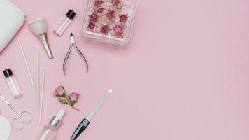 arranjo de acessórios para unhas em fundo rosa foto