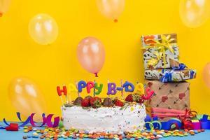vista frontal do bolo de aniversário com presentes em fundo amarelo vibrante foto