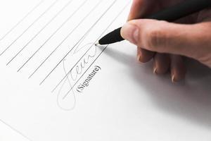 mão assinando documento com caneta, close-up foto