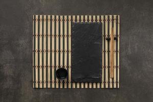 configuração de mesa com pauzinhos em tapete de bambu foto