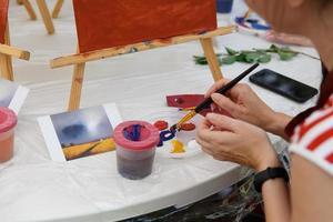closeup da mão de uma artista feminina pintando um quadro em uma paleta na oficina foto