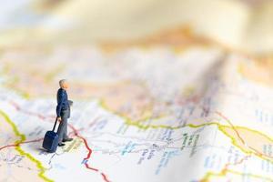 empresário em miniatura no mapa, conceito de viagens foto