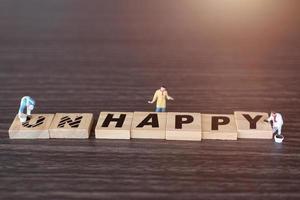 pessoas em miniatura, equipe de trabalhadores em blocos de madeira com a palavra infeliz com o prefixo não riscado, deixando a palavra feliz