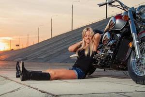 loira sexy sentada perto de sua motocicleta foto