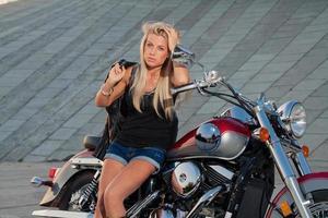 loira sexy sentada em sua motocicleta foto