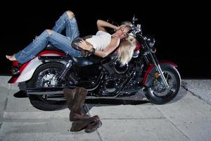 loira sexy deitada em sua motocicleta foto