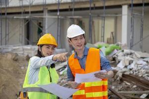 gerente de engenheiro inspeciona canteiros de obras e verifica as plantas no projeto de construção de residência urbana foto